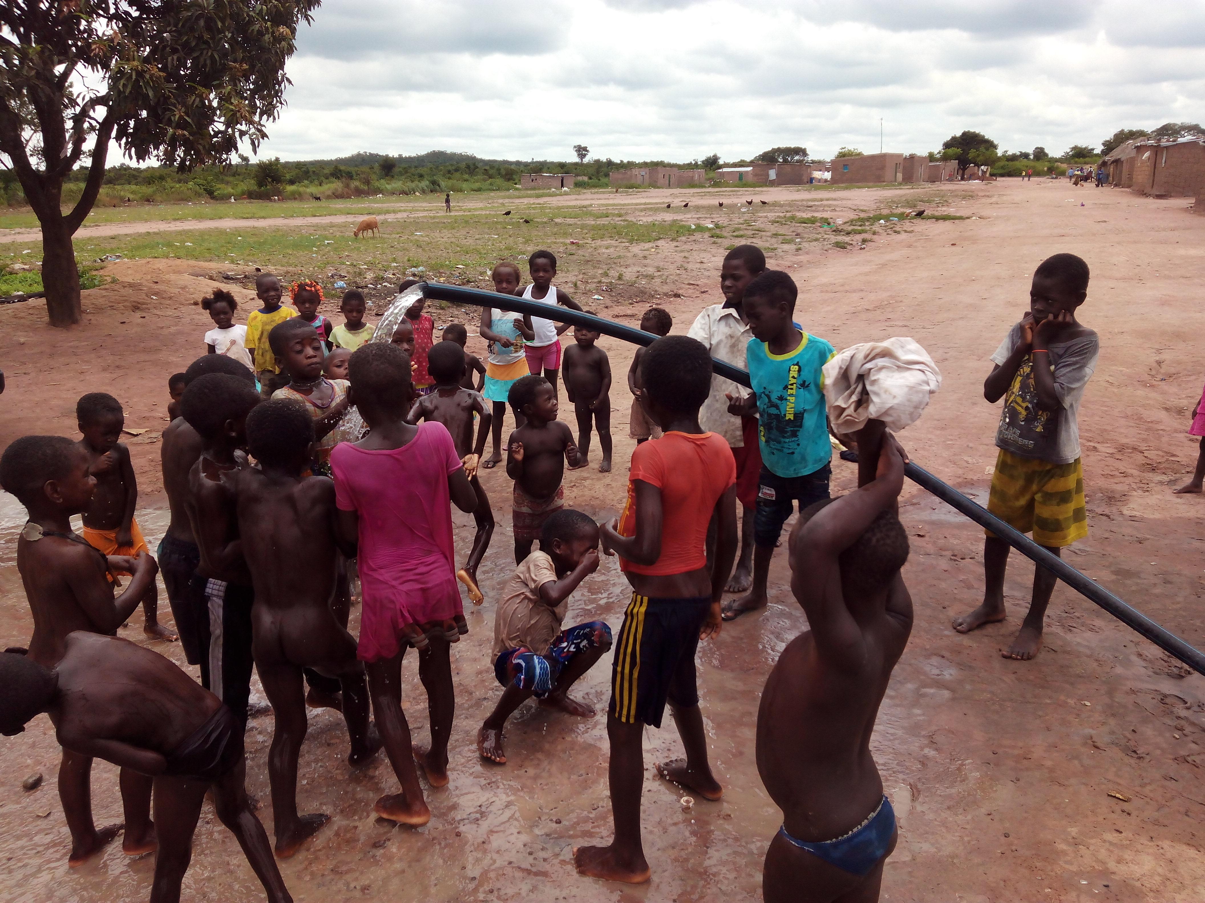 Los niños disfrutan del agua que por primera vez sale en su población